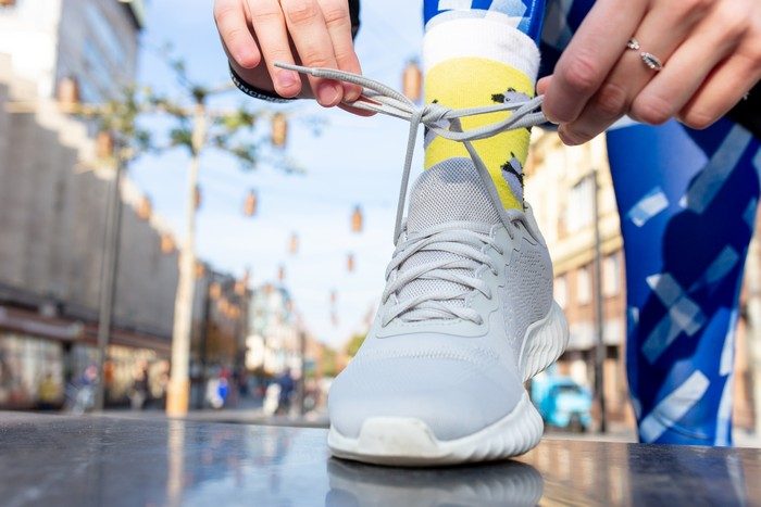 sporty woman tying shoelace on sneakers before training. female athlete preparing for jogging outdoors.