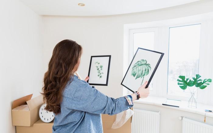 haus renovieren neue möbel und deko wählen holzprofi 24 junge frau hält zwei bilder weises zimmer