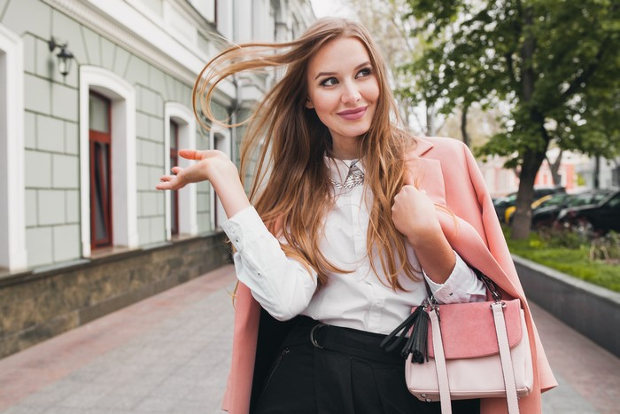 cute attractive stylish smiling woman walking city street in pink coat spring fashion trend holding purse, elegant style
