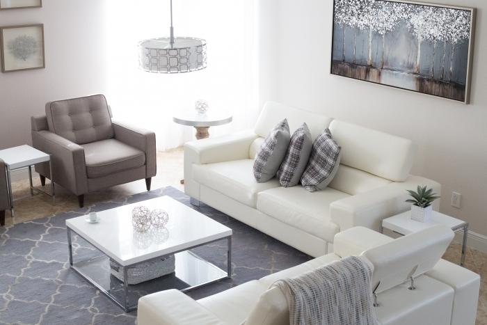 raumakustik optimieren schallabsorber deckenplatten aufhängen polstermöbel weiße sofa kaffeetisch