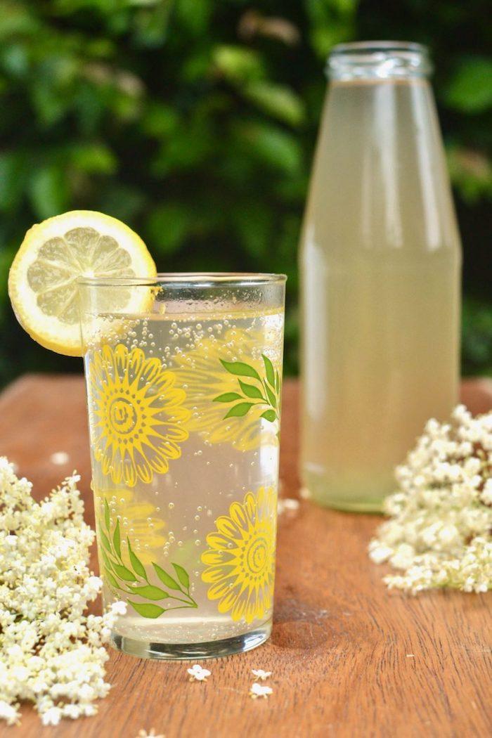 holunderblütensirup gesund ein brett aus holz ein glas mit einem gelbem holunderblütensirup mit geschnittener zitrone