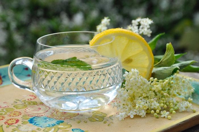 holunderblütensirup ohne zucker selber machen brett aus holz ein glas mit holunderblütensirup und frischer geschnittener zitrone