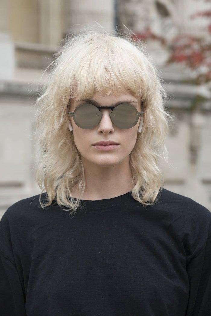 ausgefallene runde sonnenbrillen basic casual style schwarze bluse frau mit blonden haaren modern shag frisur