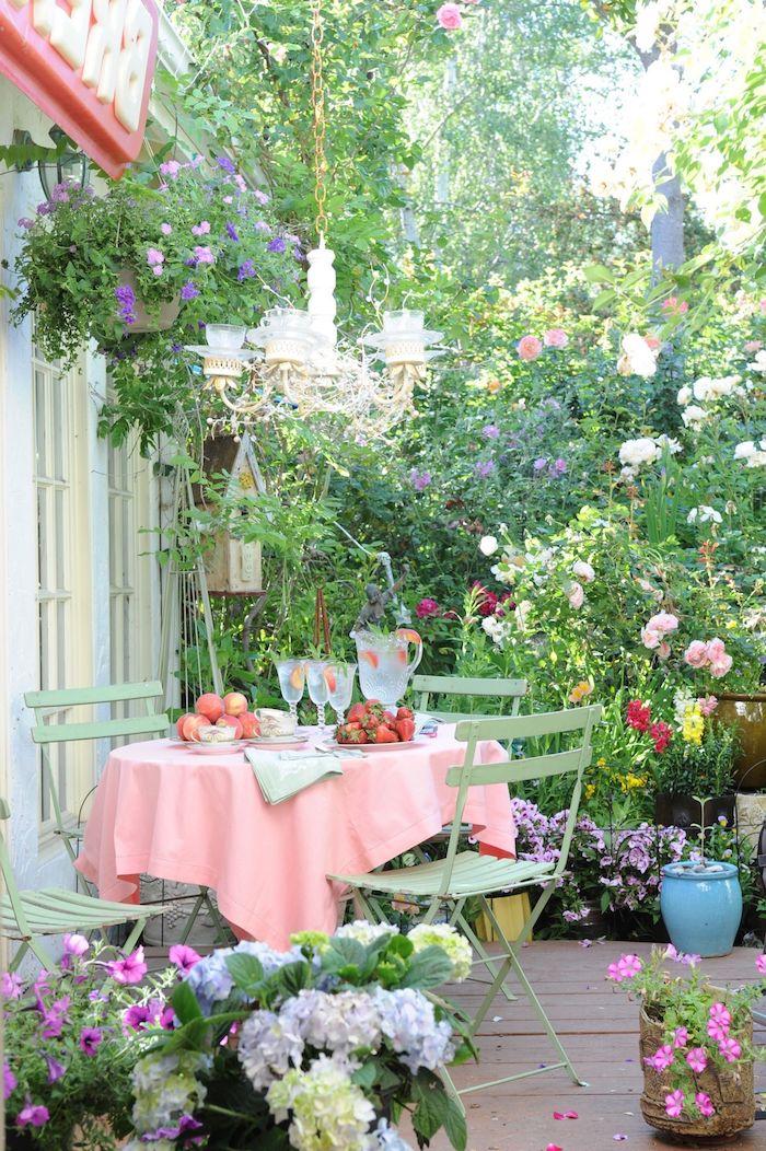 außeneinrichtung kleiner garten ideen runder tisch rosa tischdecke grüne stühle viele blumen und grüne pflanzen