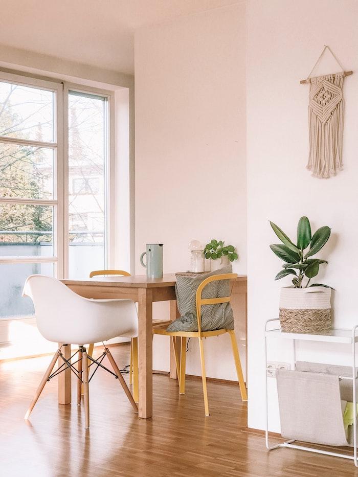 blass pinke wandfarbe kleiner holztisch mit verschiedenen stühlen essplatz ideen wenig platz makramee an der wand grüne pflanze