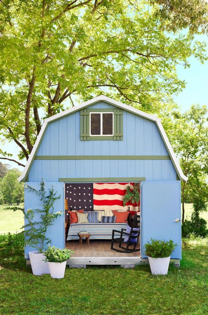blaues kleines gartenhaus umgewandelt in einem zimmer große amerikanische flagge großes bett bunte deko kissen