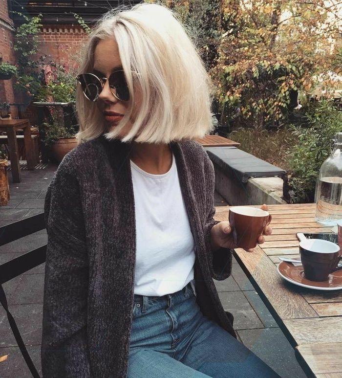 blonde frau sitzt in einem caffe platinblonde haare legeres outfits weißes t shirt strickjacke und jeans blunt bob schneiden