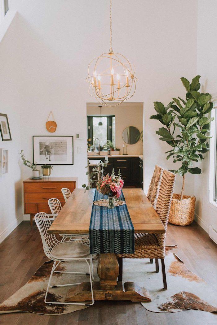 böhmische inneneinrichtung wohn esszimmer einrichten großer esstisch verschiedene stühle vintage schrank große grüne pflanze pendelleuchte mit kerzen