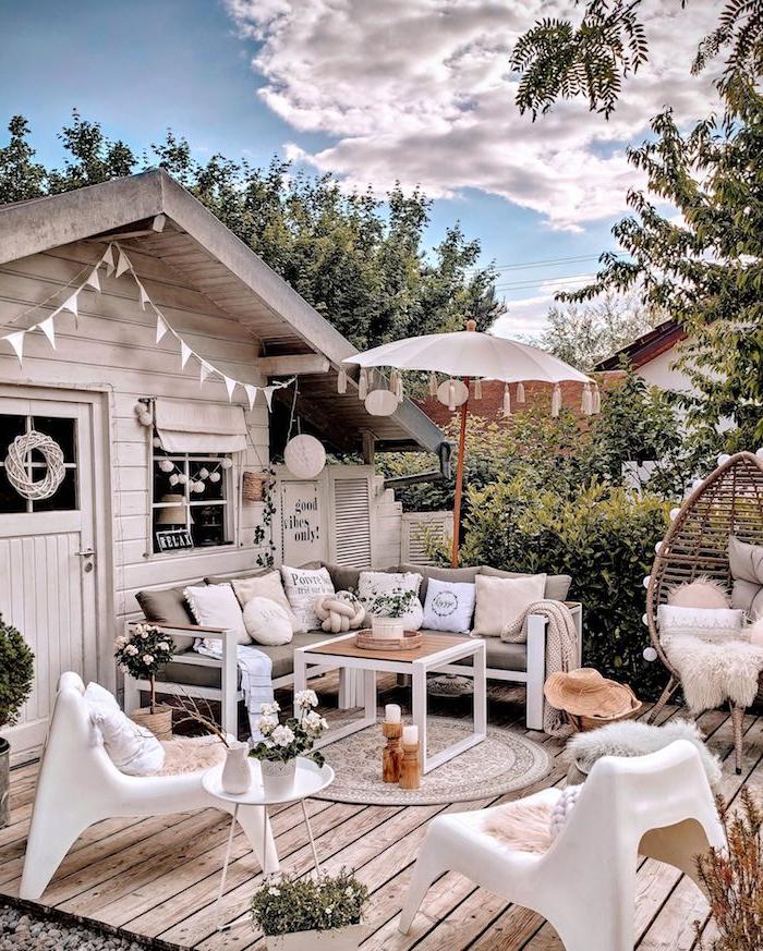 boho chic gartenhaus mit terrasse stylischer schirm ecksofa mit deko kissen runder teppich dekorative fahnen