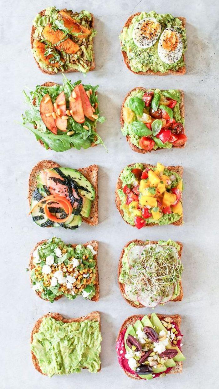 brotscheiben als beilagen zum gegrillten gleisch salate mit avocado tomaten gurken paprikas und rucola