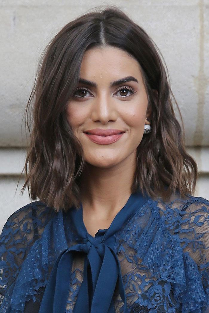 camila coelho street style elegante blaue bluse mit schleife model mit braunen gewellten haaren bob dünnes haar inspo schön geschminktes gesicht