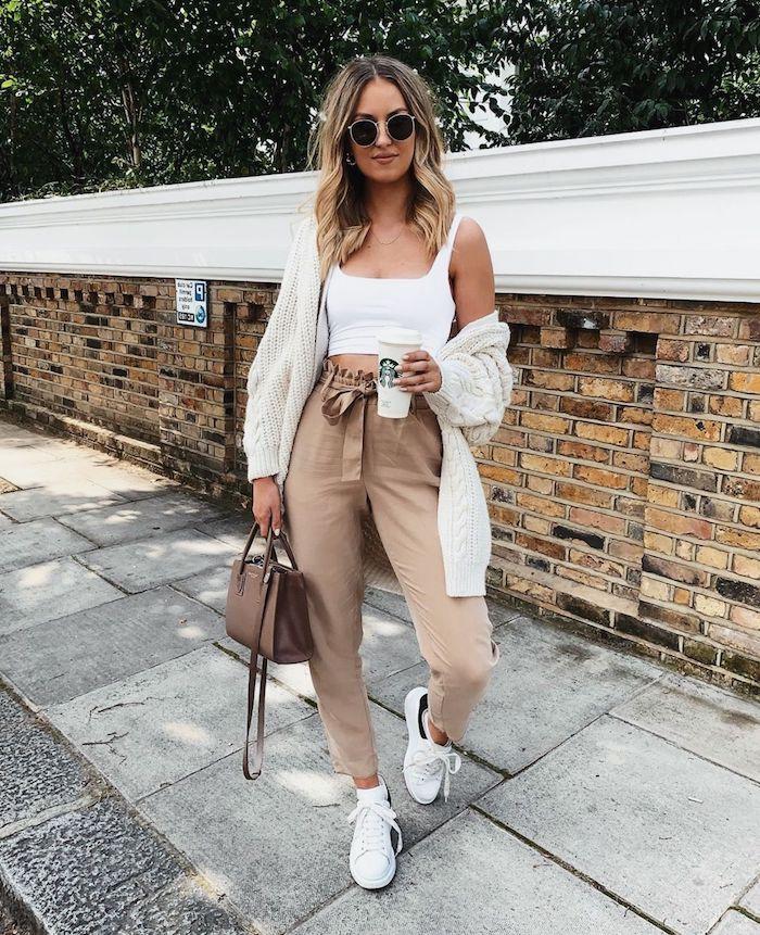 casual street style inspo weißes crop top paperbag hose beige style mit weißen sneakers und strickjacke mini tasche frau mit blonden haaren