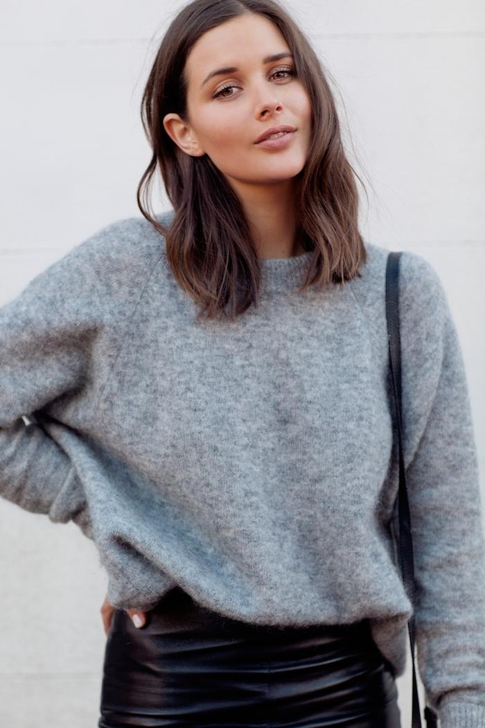 casual style outfit schwarzer lederrock kombiniert mit weitem grauen pullover frisuren mittellange haare