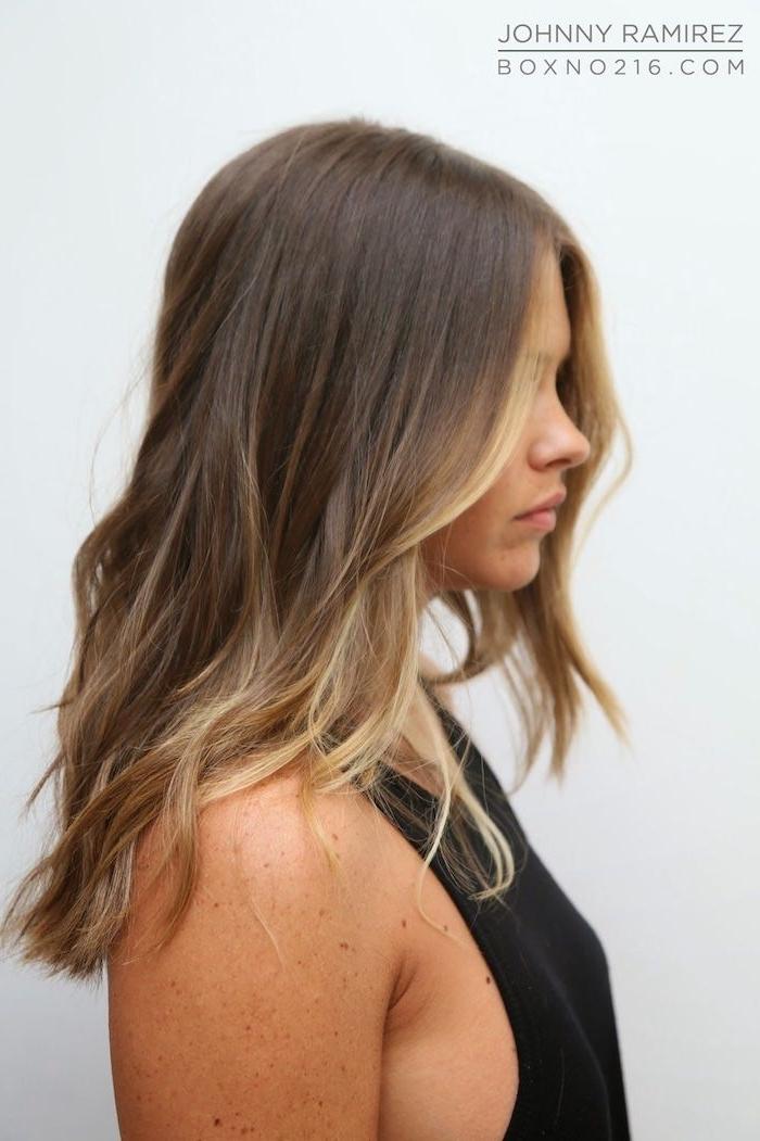 dame im schwarzen sommertop lange haare mit highlights vorne braune haare mit strähnen gesichtsrahmen trend e girl