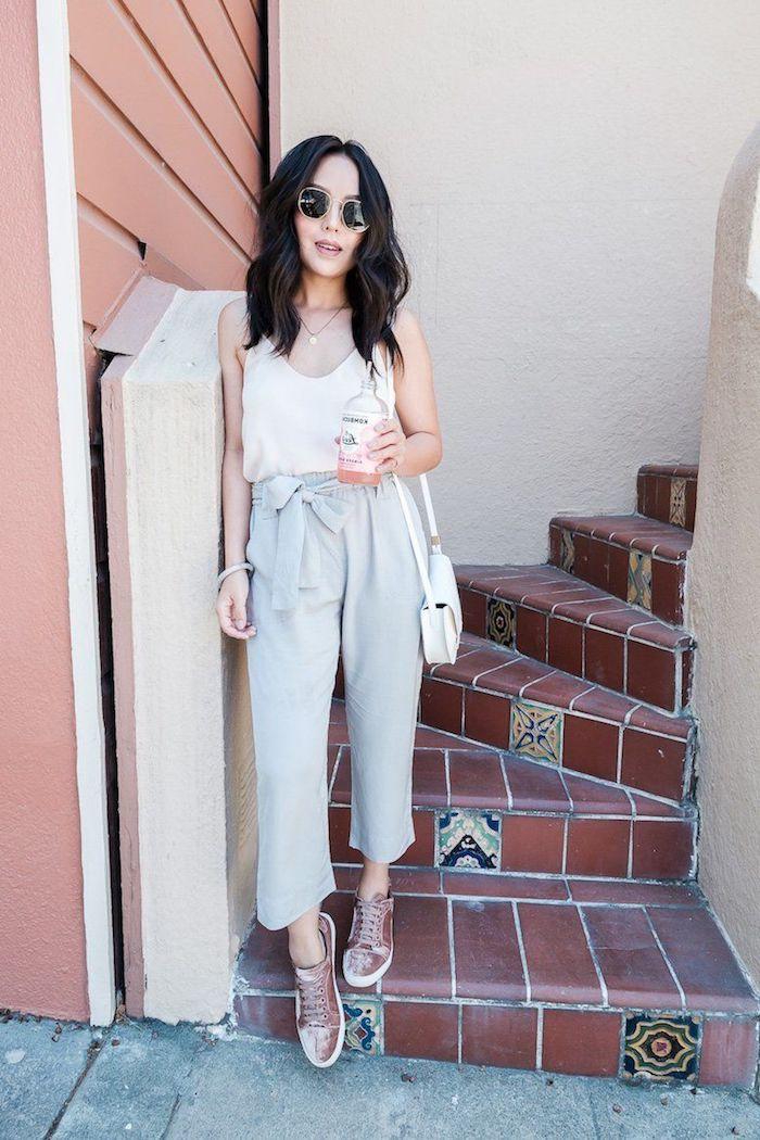 dame mit dunklen braunen haaren legeres outfit pinke sneakers graue paperbag hose dame gestylet mit weißem top mini umhängetasche in weiß runde schwarze sonnenbrillen