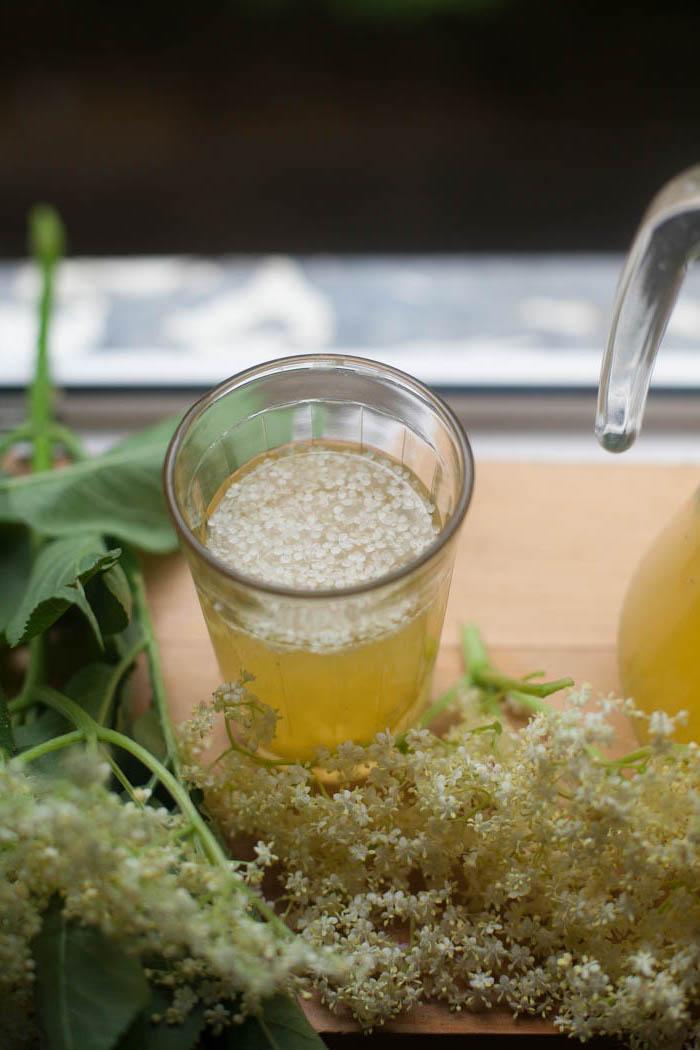 ein glas mit einem saft holunderblütensirup ohne zucker selber machen ein tisch aus holz