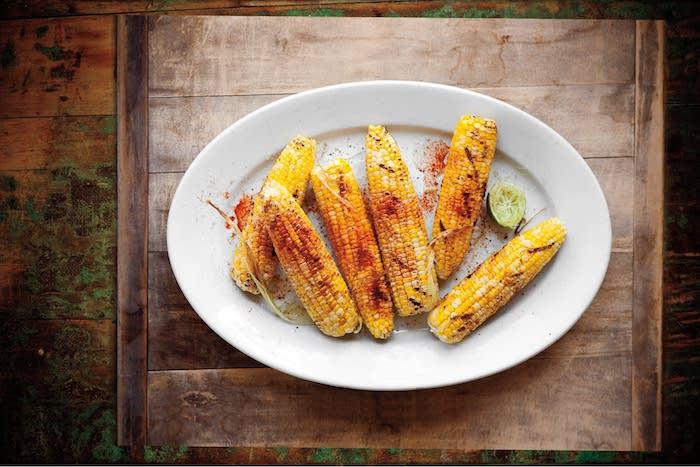 ein tisch aus holz mexikanische maiskolben kochen tipps weiße schüssel mit scharfen maiskolben mit butter und limette