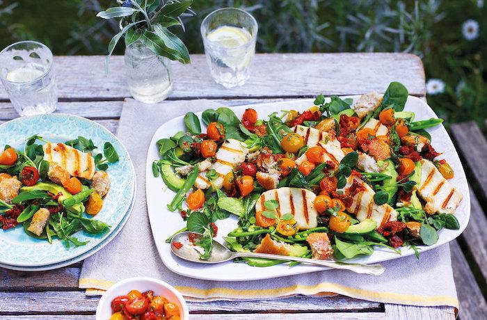 ein weißer teller mit salat zum grillen ein tisch aus holz ein glas mit wasser blauer teller party salate zum grillen