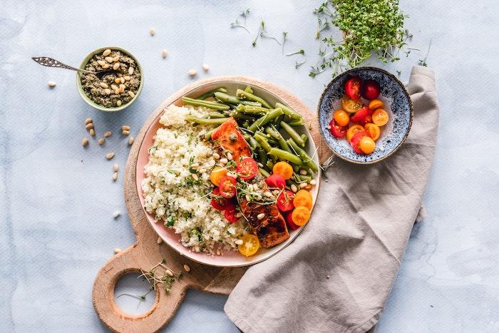 eine beige decke ein brett aus holz welche salate passen zum grillen eine schüssel mit fleisch und tomaten