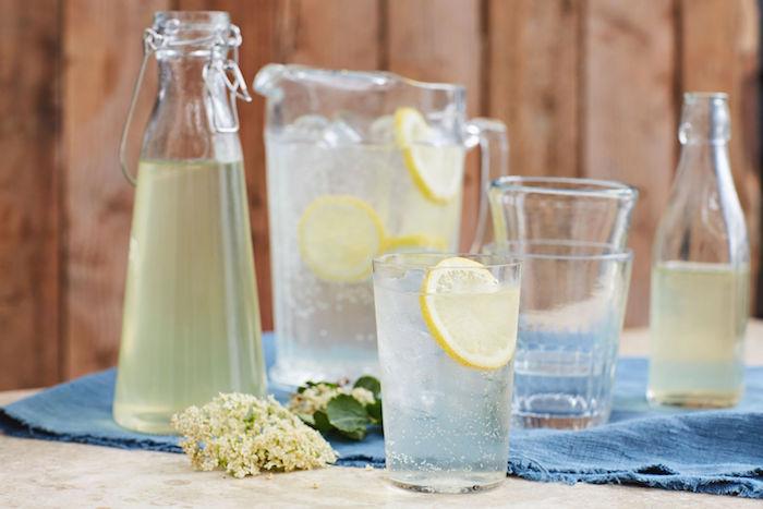 eine blaue decke eine flasche und glas mit saft tisch aus holz holunderblütensirup ohne zucker selber machen