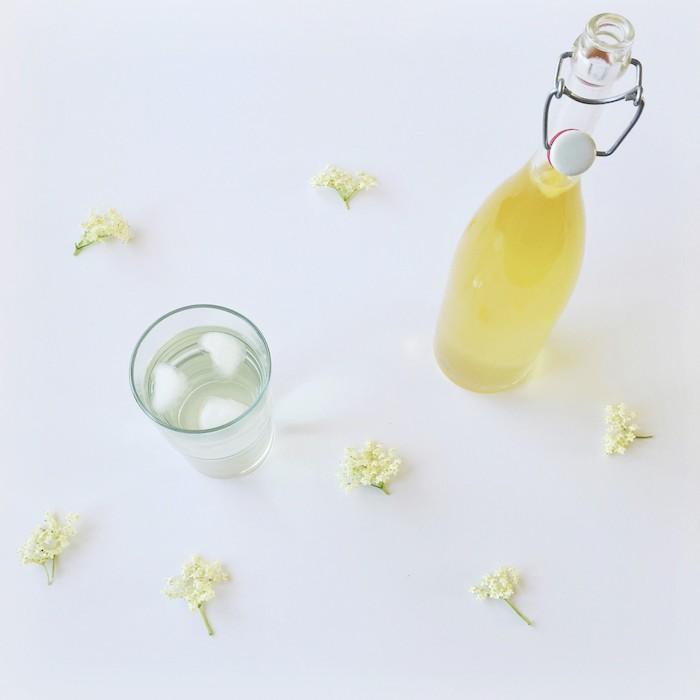 eine flasche mit saft ein glas mit holunderblütensirup ohne zucker