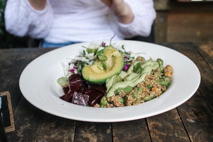 eine frau party salate zum grillen ein weißer teller mit einem salat mit avocado pesto und chia