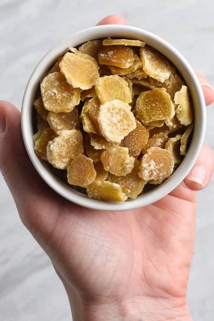 eine hand mit einer weißen schüssel mit kandierter ingwer mit zucker einfache rezepte kandierte frücchte