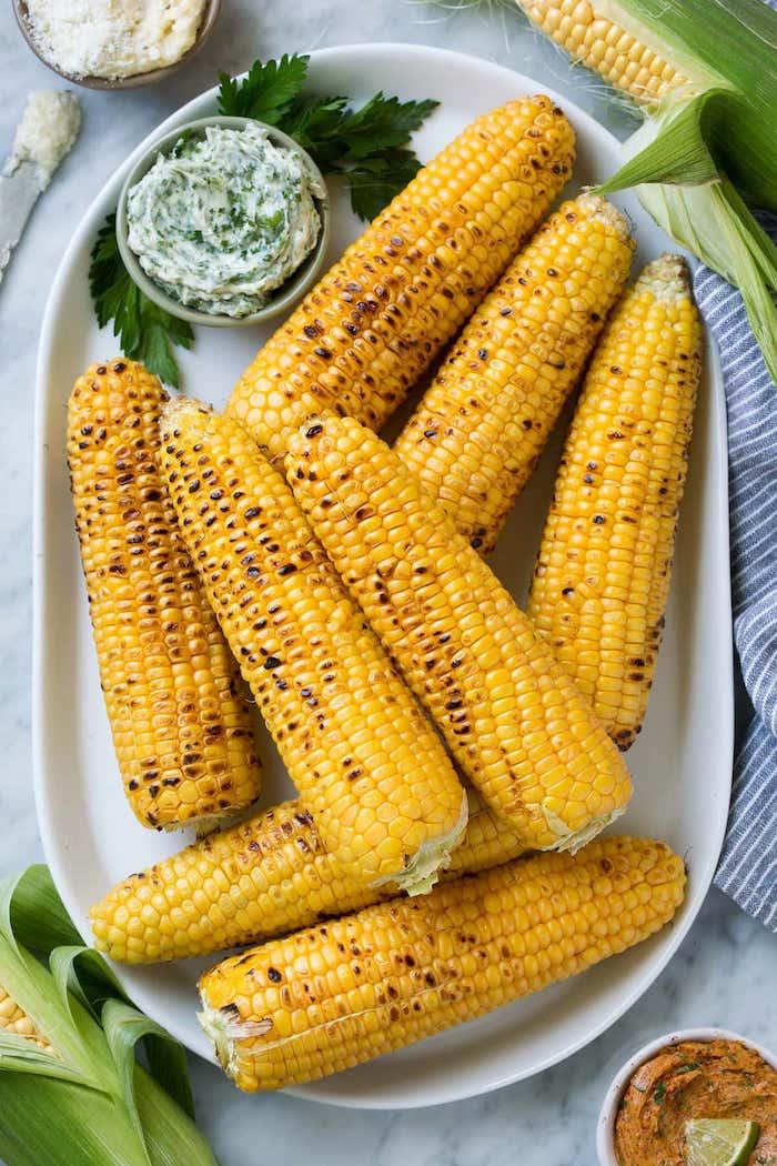 eine schüssel mit butter aus bärlauch gekochte maiskolben mit käse petersilie gewürzen und scharfen roten paprikas mexikanische gerichte