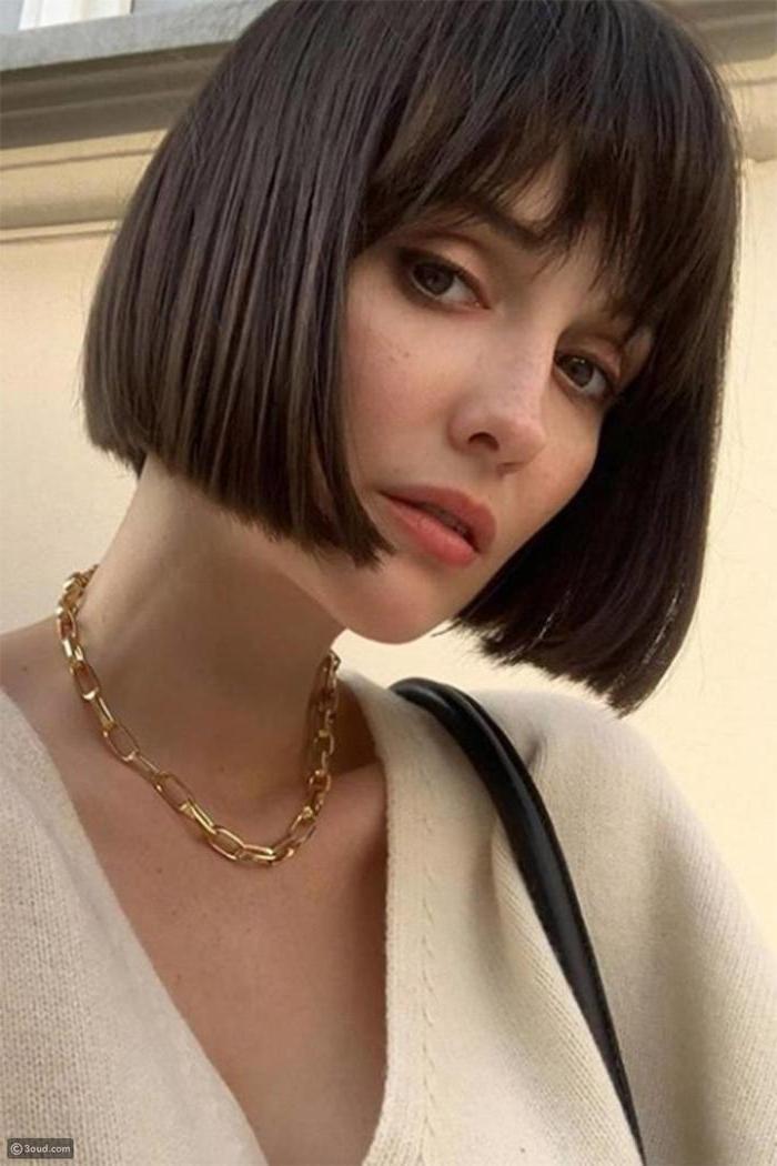 elegante dame goldene halskette klassische kurzhaarfrisuren mit pony blunt bob schneiden inspiration minimalistisch geschminktes gesicht schwarze handtasche