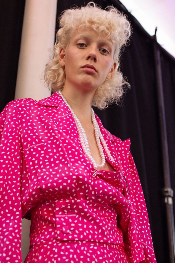 elegantes outfit pinkes kleid mit weißen punkten lockige mullet frisur ausgefallene haarschnitte inspiration