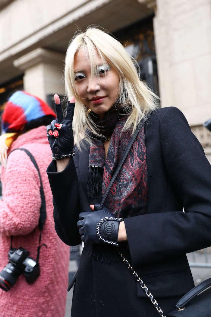 fashion week street style inspo schwarzer mantel chanel handschuhe bunter schal frau mit blonden haare macht friedenszeichen shag frisu mit pony