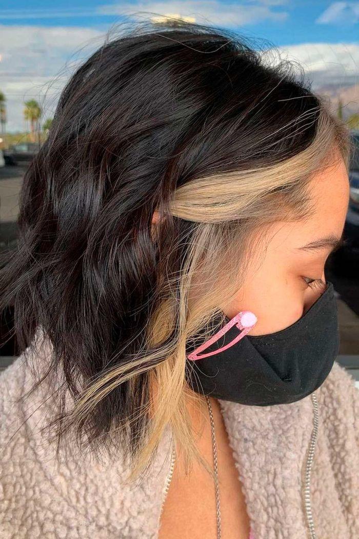 frau mit schwarzer schutzmaske kurzer haarschnitt gewellt braune haare blonde strähnen vorne trendige haarfarben 2021 flausche beige jacke
