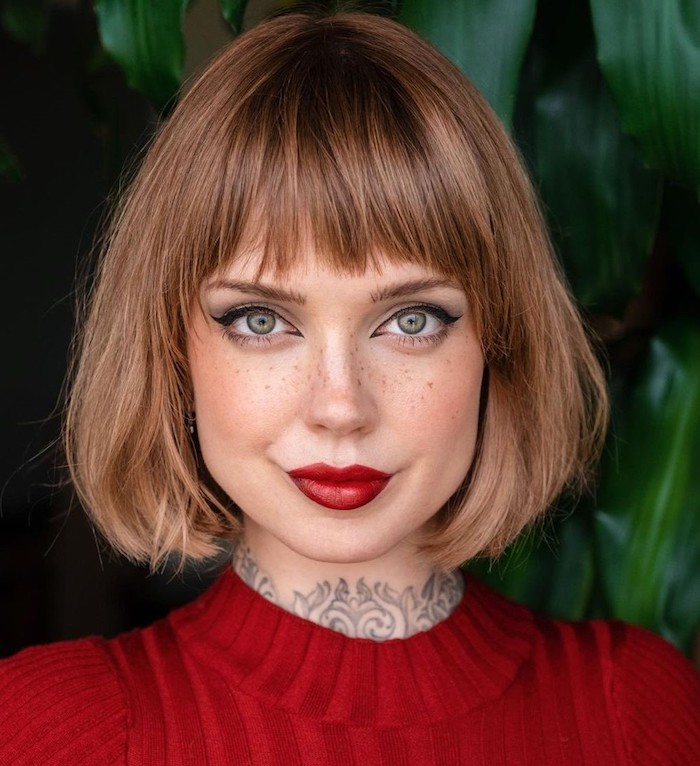 freche kurzhaarfrisuren mit pony rot blonde haare kurz make up katzenaugen und roter lippenstifft tattoos am nacken rote bluse