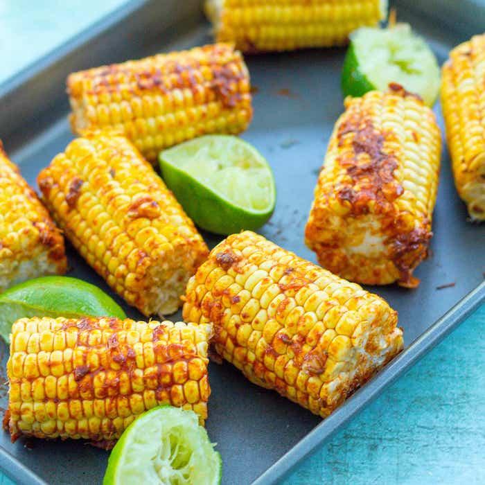 frische geschnittene limette mexikanische gerichte mit gegrilltem maiskolben gekochte und gegrillte maiskolben