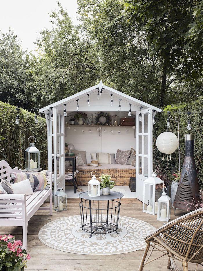 gartenhaus mit terrasse boho chic stil schwarzer runder korbtisch beiger teppich kleines häuschen mit bett und deko kissen hängede kleine lampen