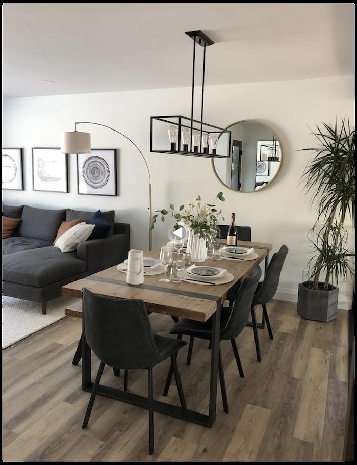 gedeckter tisch schwarze essstühle runder spiegel schwarzer eckcouch wohnzimmer mit essbereich kleine wohnung einrichten dekoration grüne pflanze