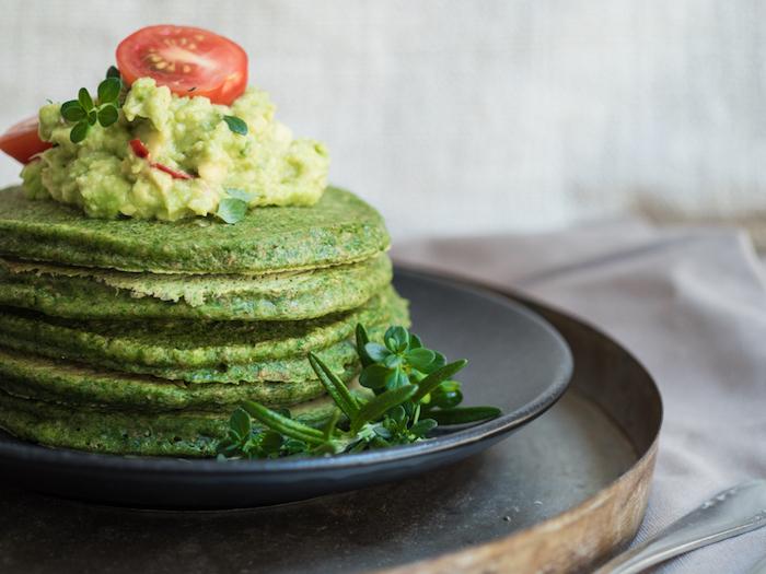 gefüllte pfannkuchen spinat pfannkuchen mit spinat avocado und tomaten auf schwarzem teller