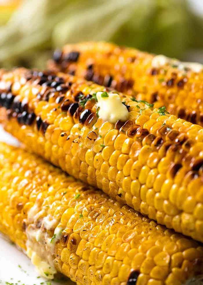 gelben maiskolben mit geschmolzener butter und gehackter petersilie mexikanische gerichte mit gegrilltem und gegkochtem maiskolben
