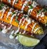 geschnittene limette gekochte maiskolben mit käse petersilie gewürzen und scharfen roten paprikas salate zum kochen