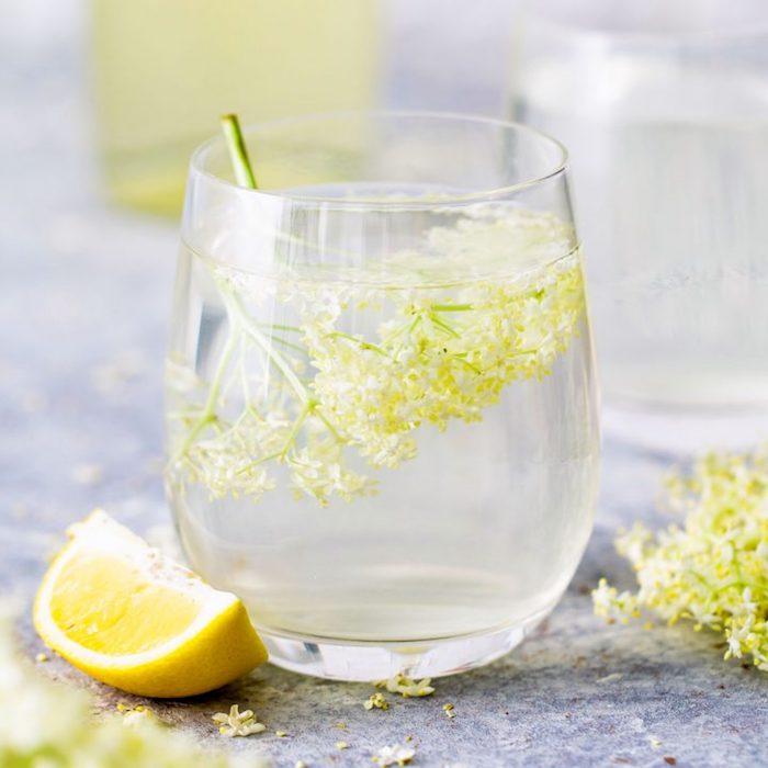 glas mit frischem holunderblütensirup ohne zucker eine gelbe geschnittene zitrone