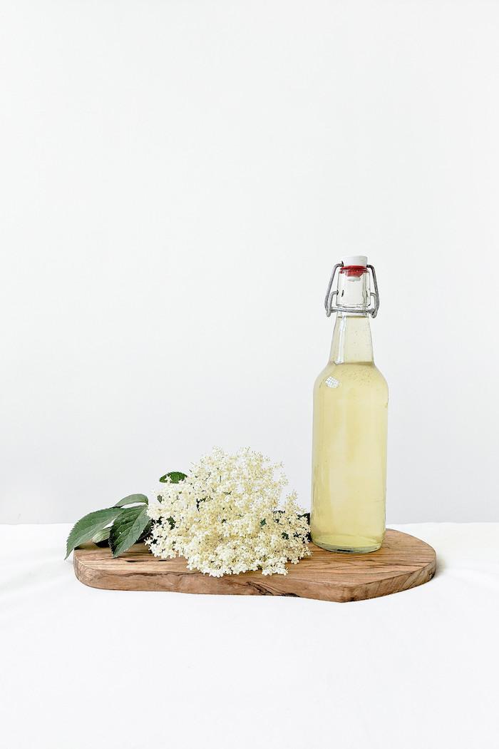 grüne blätter ein brett aus holz holunderblütensirup selber machen eine flasche mit gelbem holunderblütensirup