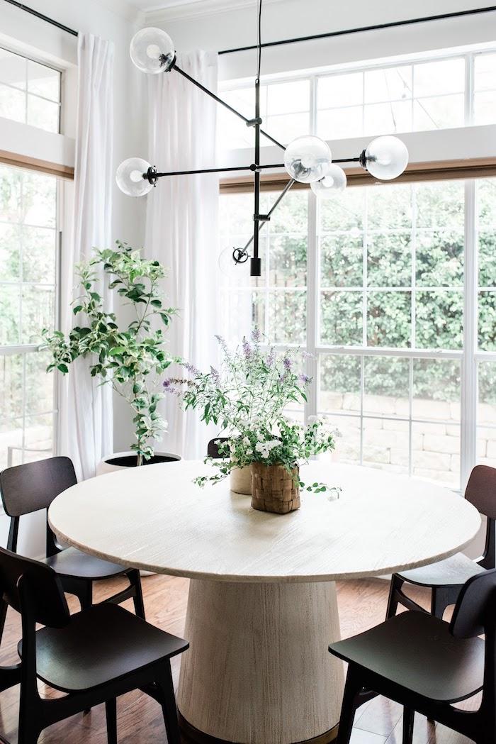 grüne pflanzen dekoration wohn esszimmer schwarze moderne stühle massiver runder tisch aus holz interior design inspiration