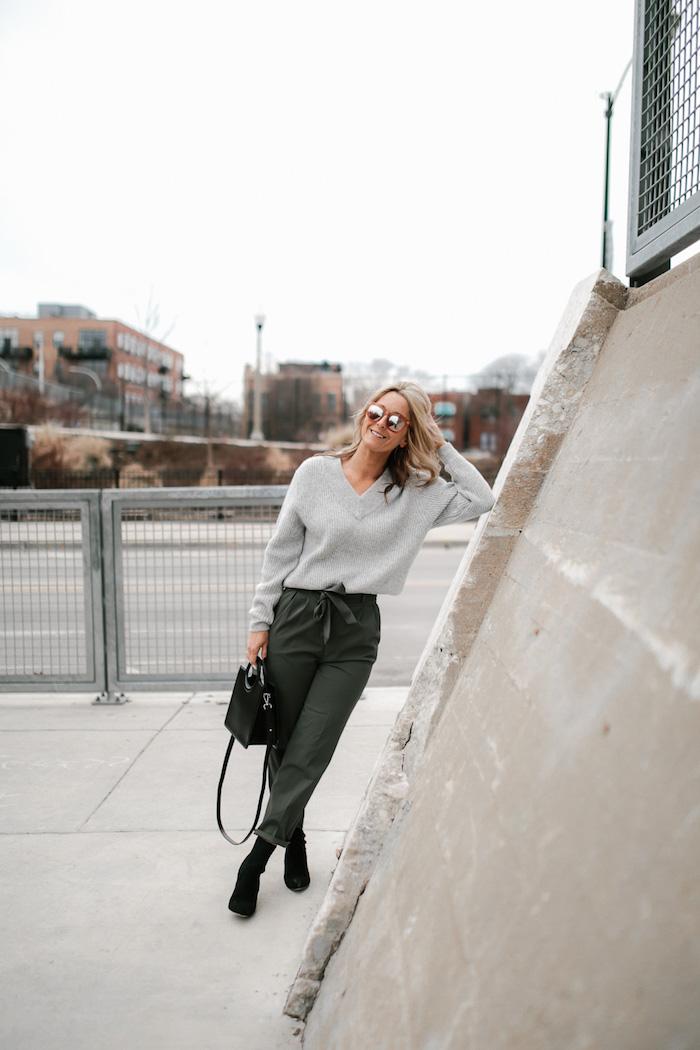 herbst street style inspiration dunkel grüne paperbag hose damen gestylt mit grauem weiten pullover schwarze boots und tasche