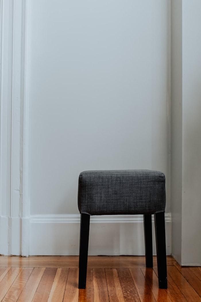 hocker grau sitzhocker viereckig holzbeine fußhocker grau grauer hocker akleidezimmer korridor weiße wände