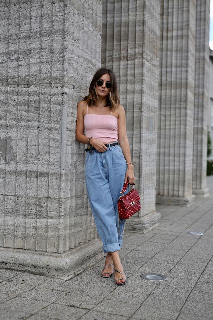 ideen für paperbag hose kombinieren jeans mit hohem bund pinkes crop top mit spaghettiträgern elegante rote tasche mittellange braune haare mit highlights