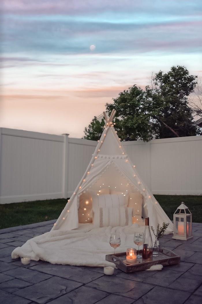 kleiner romantischer garten weißes zelt mit hängeleuchten weiße flauschige decke angezündete kerze zwei weingläser