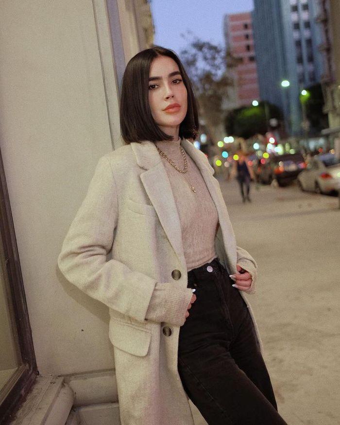 kurze schwarze haare blunt bob frisur 2021 angesagte kurzhaarschnitte sommerfrisuren inspo grauer mantel und bluse schwarze jeans goldene halskette