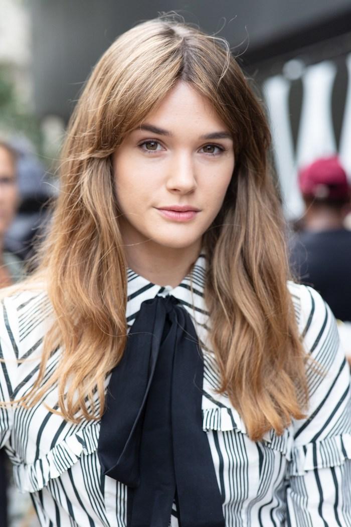 lange dunkelblonde haare mit strähnen schwarz weiße bluse mit schleife elegantes styling modern shag haarschnitt inspiration
