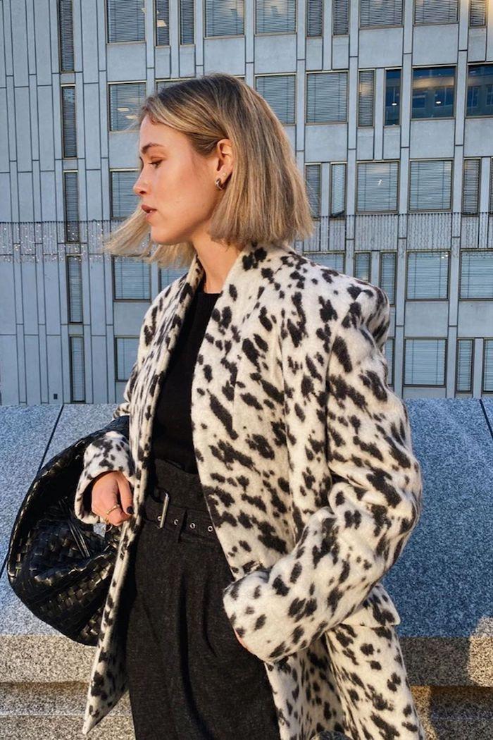 langer schwarz weißes mantel mit tier moven schwarzes outfit und große handtasche blunt bob schneiden ideen dame mit kurzen blonden haaren