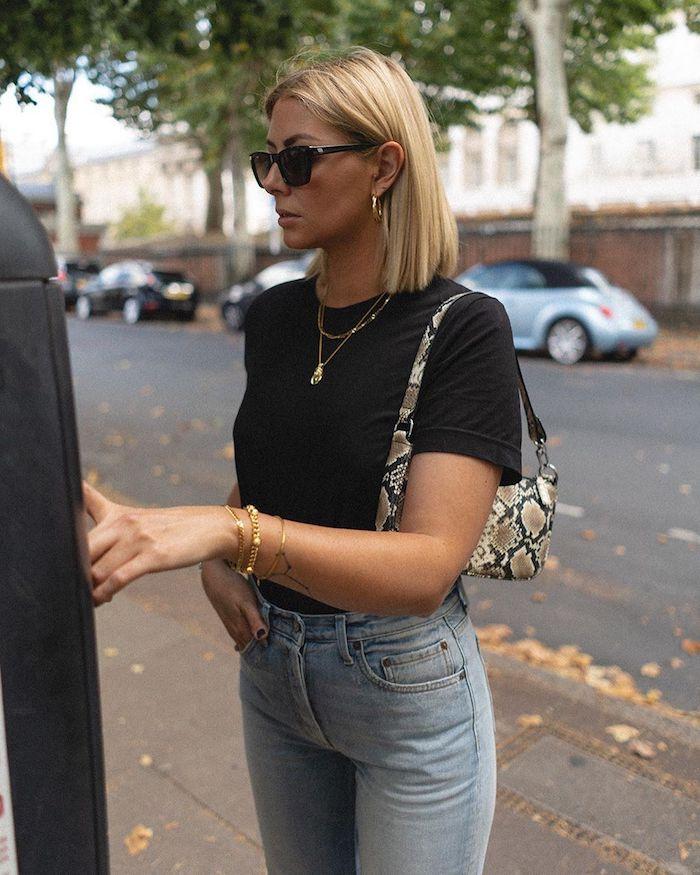 legeres street style outfit schwarzes t shirt und blaue jeans mini handtasche blonde frau mit kurzen haaren blunt bob frisuren mittellang bob